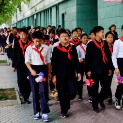 Junge Pionieren laufen singend durch die Stadt.